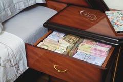 Paquetes de billetes de banco en mesita de noche Imágenes de archivo libres de regalías
