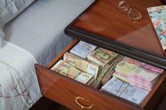 Paquetes de billetes de banco en mesita de noche Fotografía de archivo libre de regalías
