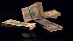 Paquetes de 100 cuentas de USD que caen y que despiden metrajes