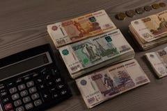 Paquetes de dinero Rublos rusas y calculadora en un fondo de madera Imágenes de archivo libres de regalías