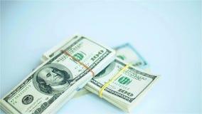 Paquetes del dólar de EE. UU. que caen en la superficie blanca Salarios, arnings, ganancias almacen de metraje de vídeo