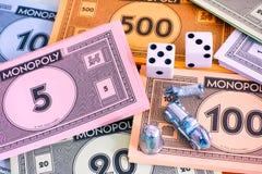Paquetes del dinero del monopolio con los símbolos y los dados Fotos de archivo
