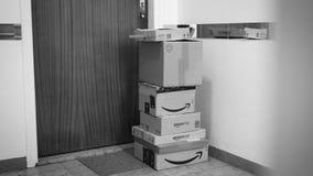 Paquetes múltiples de la cartulina del Amazon Prime cerca de la puerta del apartamento metrajes