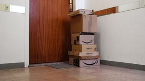 Paquetes múltiples de la cartulina del Amazon Prime de la inclinación-para arriba cerca de la puerta del apartamento almacen de video