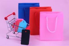 paquetes para las compras y una carretilla de las compras dentro con diversas etiquetas y precios en un fondo rosado brillante co fotografía de archivo libre de regalías