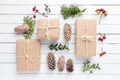 Paquetes rústicos envueltos hechos en casa del papel marrón con diversas cosas naturales en la superficie de madera blanca Imagen de archivo libre de regalías