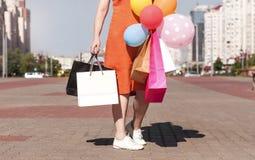Paquets avec des achats dans les mains d'une fille marchant par le Th Photos stock
