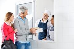 Paquets de achat de pâtes de couples heureux des chefs Image stock