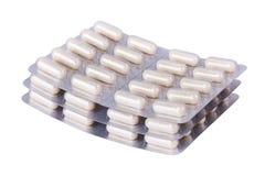 Paquets de pile de boursouflure de pilules blanches sur le fond blanc photos libres de droits
