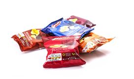 Paquets des pommes chips de Snackrite sur un fond blanc image stock