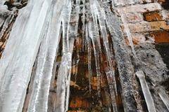 Paquets et glaçons de glace de plan rapproché, vieux fond abstrait de mur de briques avec de la glace de fente, mousse, et branch Photographie stock