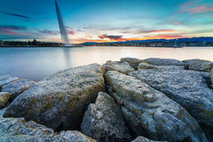 Sunset on Lake Geneva in Geneva, Switzerland. View of the lighthouse at Bains des Paquis and lake Geneva at sunrise with Sunstar in Geneva city, Switzerland. The Stock Image