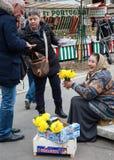 La mujer mayor sonriente vende narcissuses amarillos a los compradores en el mercado Fotografía de archivo