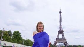 PARÍS, FRANCIA CIRCA agosto de 2017: Mujer turística sonriente con la bandera francesa cerca de la torre Eiffel en París almacen de video