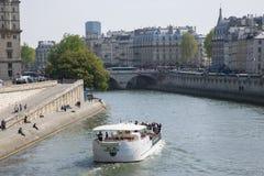 París, Francia - 17 de abril de 2011: Un barco de placer navega a lo largo del río el Sena en un día de verano fotografía de archivo