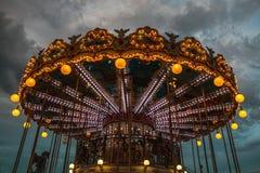 PARÍS, FRANCIA - 30 DE AGOSTO DE 2015: Carrusel francés viejo en un parque del día de fiesta en el tiempo de verano de la noche Imagen de archivo libre de regalías