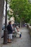 PARÍS, FRANCIA - 29 DE MARZO DE 2014: Mujeres que se sientan leyendo un libro en el río Sena Imagen de archivo