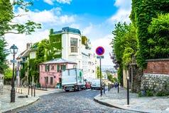París, Francia - 27 de mayo de 2015: calle en París en el área de Montmartre en un día soleado con árboles verdes y un cielo azul Fotografía de archivo libre de regalías