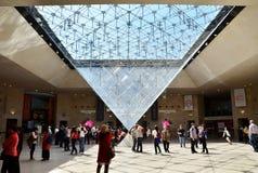 París, Francia - 13 de mayo de 2015: Los turistas visitan dentro de la pirámide de las lumbreras Imágenes de archivo libres de regalías