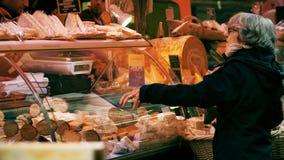 PARÍS, FRANCIA - 7 DE OCTUBRE DE 2017 Cliente femenino mayor en la parada del queso en el mercado local de la comida imagen de archivo libre de regalías