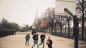 PARÍS, FRANCIA - DICIEMBRE, 31, 2016 Adolescentes masculinos de Multinatonal que juegan a baloncesto de la calle contra torre Eif Imágenes de archivo libres de regalías