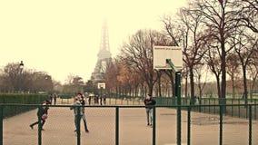 PARÍS, FRANCIA - DICIEMBRE, 31, 2016 Adolescentes masculinos de Multinatonal que juegan a baloncesto de la calle contra torre Eif Foto de archivo