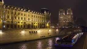 PARÍS, FRANCIA - DICIEMBRE, 31, 2016 Barco turístico de río Sena y la fachada occidental de la catedral famosa de Notre Dame Imagen de archivo
