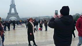 PARÍS, FRANCIA - DICIEMBRE, 31, 2016 El sombrero que lleva hermoso de la mujer joven presenta cerca de torre Eiffel en un día de  Foto de archivo