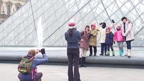 PARÍS, FRANCIA - DICIEMBRE, 31, 2016 Familia alegre que presenta y que hace las fotos cerca del Louvre, museo francés famoso Imagen de archivo libre de regalías