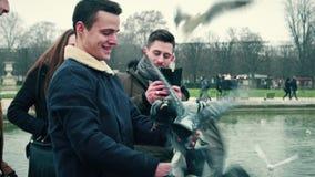 PARÍS, FRANCIA - DICIEMBRE, 31, 2016 Gente joven que alimenta las palomas y que presenta en parque parisiense Foto de archivo