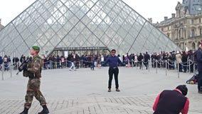 PARÍS, FRANCIA - DICIEMBRE, 31, 2016 Turista que presenta y que hace las fotos cerca del Louvre, museo francés famoso, popular Fotografía de archivo