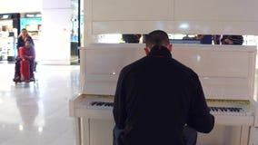 PARÍS, FRANCIA - ENERO, 1, 2017 Steadicam tiraron al hombre que jugaba el piano en área con franquicia de las tiendas en el aerop almacen de metraje de vídeo
