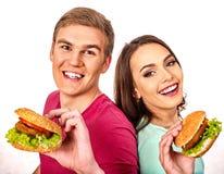 Par äter hamburgaren Kvinnor och mantagandesnabbmat arkivbild