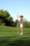 Par. A woman holds the pole for a golfer Royalty Free Stock Image