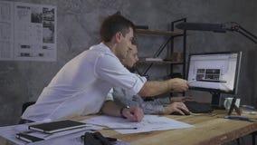 Par av anställda arbetar på övertid på datoren, diskuterar det arkitektoniska planet av gården, på tabelllögnlegitimationshandlin stock video