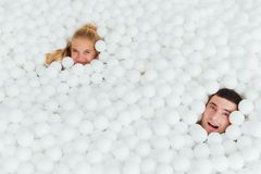 Par av att älska vänner har gyckel som omges av vita plast- bollar i en torr simbassäng royaltyfri bild