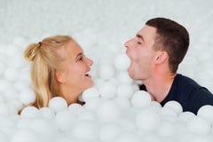 Par av att älska vänner har gyckel som omges av vita plast- bollar i en torr simbassäng Royaltyfria Bilder