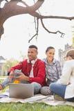 Par av att le studenter som sitter under trädet fotografering för bildbyråer