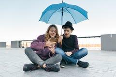 Par av att le tonåriga vänner som sitter under ett paraply och ser smartphonen, livsstil av tonåringar i staden arkivbild