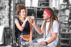Par av att skratta flower-power-folket som dricker tequilautgifternatt i bar arkivbild