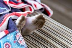 Par av barnfot i smutsiga nedfläckade vitsockor Nedsmutsade sockor för unge, medan spela utomhus Barnkläder som bleker och tvätta royaltyfri foto