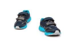 Par av blått och svarta sportiga skor för unge Arkivfoton