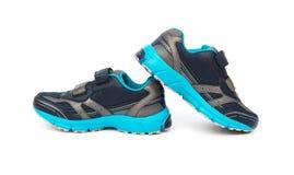 Par av blått och svarta sportiga skor för unge på vit Arkivfoto