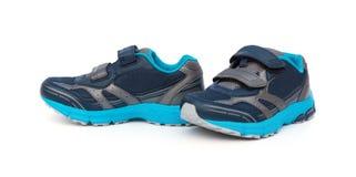 Par av blått och svarta sportiga skor för unge på vit Royaltyfria Foton