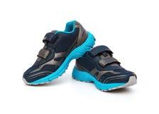 Par av blått och svarta sportiga skor för unge på vit Arkivbild