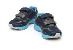 Par av blått och svarta sportiga skor för unge på vit Royaltyfri Bild