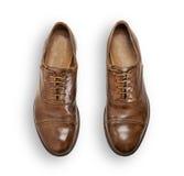 Par av bruna lädermanskor som isoleras på vit Fotografering för Bildbyråer