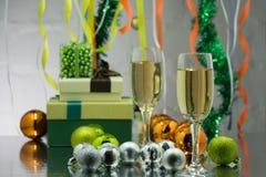 Par av champagneexponeringsglas och tomteblosset, julgranprydnad som bakgrunden Arkivfoton