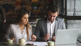 Par av coworkers som diskuterar arbetsprojekt, medan sitta på väntande på lunch för kafé lager videofilmer