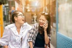 Par av den asiatiska kvinnan som skrattar med lyckasinnesrörelse Arkivfoto